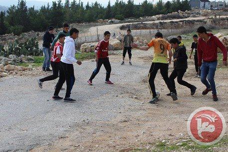 הילדים משחקים כדורגל. ברקע בתי התנחלות סלעית