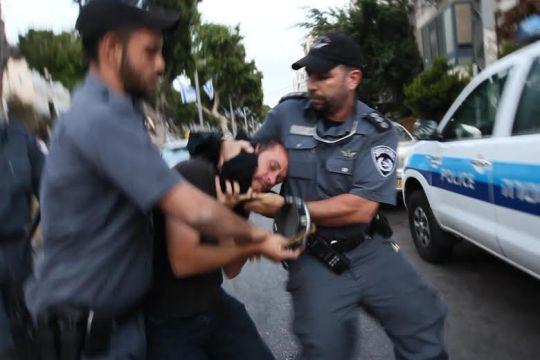 נדב פרנקוביץ' מובל באלימות לניידת המשטרה (צילום: מנחם ברגר)