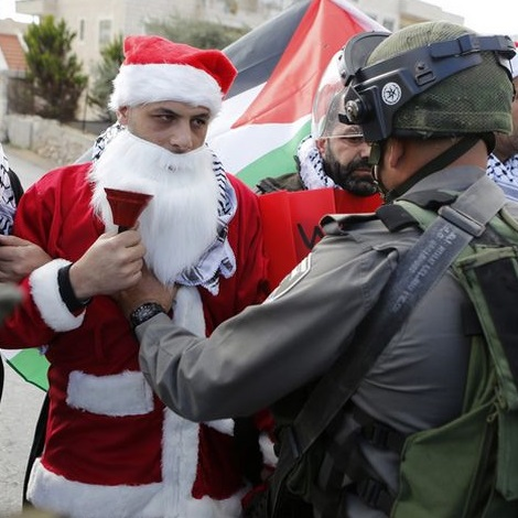 A Palestinian protester dressed in a Santa Claus costume argues with an Israeli border policeman during a demonstration in the West Bank city of Bethlehem