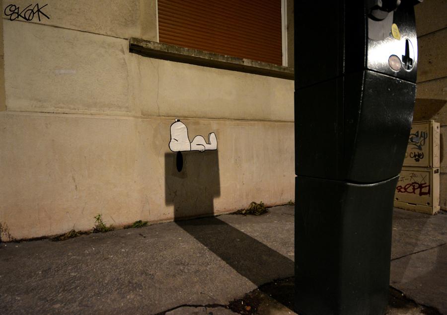 סנופי ישן על צל של מדחן. יצירה של אמן הרחוב הצרפתי OakoAk